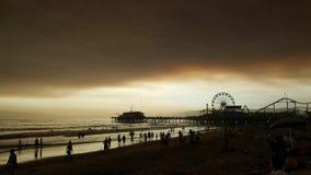 Playa en la puesta del sol con la capa de nubes oscura fotografía de archivo