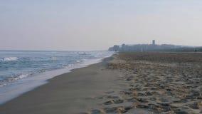 Playa en la puesta del sol con la ciudad en el fondo almacen de video