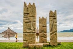 Playa en mún tiempo Vacío, altas ondas, parasoles hechos de materiales naturales, estatuas y muchacho Imagen de archivo