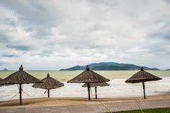 Playa en mún tiempo Vacío, altas ondas y parasoles hechos de materiales naturales Fotografía de archivo libre de regalías