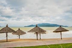 Playa en mún tiempo Vacío, altas ondas y parasoles hechos de materiales naturales Fotografía de archivo