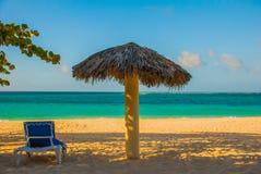 Playa Esmeralda, Holguin, Cuba. Caribbean sea: sun lounger and umbrella stand on the beach, on the background of the ocean. Sunny beautiful summer day royalty free stock photo