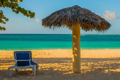 Playa Esmeralda, Holguin, Cuba. Caribbean sea: sun lounger and umbrella stand on the beach, on the background of the ocean. Sunny beautiful summer day stock photography