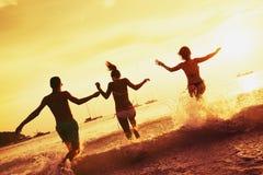 Playa feliz de la puesta del sol del mar de los amigos Imagen de archivo libre de regalías