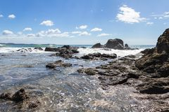 Playa Grande, Costa Rica. Relaxing beach scene in Playa Grande Costa Rica with waves crashing into the rocks with crystal clear water royalty free stock photos