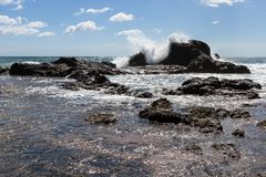 Playa Grande, Costa Rica. Relaxing beach scene in Playa Grande Costa Rica with waves crashing into the rocks with crystal clear water stock image