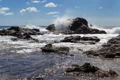 Playa Grande, Costa Rica. Relaxing beach scene in Playa Grande Costa Rica with waves crashing into the rocks with crystal clear water stock images
