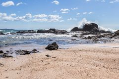 Playa Grande, Costa Rica. Relaxing beach scene in Playa Grande Costa Rica with waves crashing into the rocks with crystal clear water Stock Photography