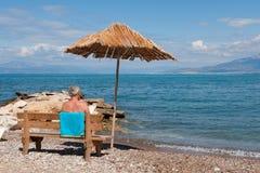 Playa griega con el hombre Imágenes de archivo libres de regalías