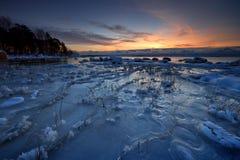 Playa helada en salida del sol. Foto de archivo