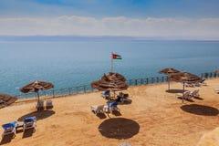 Playa hermosa con la arena y los parasoles de playa amarillos limpios en la orilla de mar muerta imagen de archivo