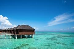 Playa hermosa con las casas de planta baja del agua en Maldivas Imagenes de archivo