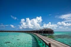 Playa hermosa con las casas de planta baja del agua en Maldivas Imagen de archivo libre de regalías