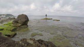 Playa hermosa con los guijarros de piedra en la isla de Rodas y el pescador solo Grecia, lapso de tiempo 4K metrajes