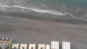 Playa hermosa de la arena del negro de Perissa, Grecia, islas de Cícladas, isla de Santorini metrajes