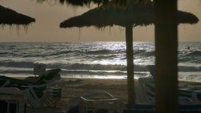 Playa iluminada por el sol en el amanecer imagenes de archivo