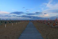 Playa Italia de Bibione con el cielo azul y las sombrillas claros Foto de archivo