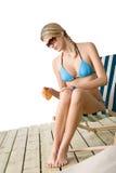 Playa - la mujer joven en bikiní aplica la loción del bronceado Foto de archivo