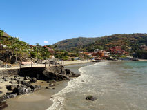 Playa La Ropa Beach, Zihuatanejo. People play in the calm waves on a clear day at Playa La Ropa Beach in Zihuatanejo Mexico Royalty Free Stock Photos