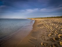 Playa larga, vacía y limpia de Stogi de la arena en la puesta del sol cerca de Gdansk, Polonia con el cielo azul dramático imagenes de archivo