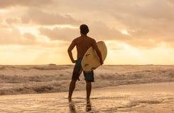 Playa masculina de la salida del sol de la puesta del sol de la persona que practica surf y de la tabla hawaiana del hombre Imagenes de archivo