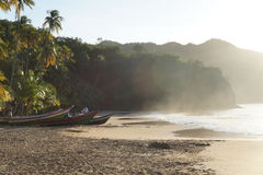 PLAYA MEDINA, caribbean beach. The sun is hidden in medina beach, under the mist of the sea, the fishermen retire from their day and leave the boats resting on Stock Photography