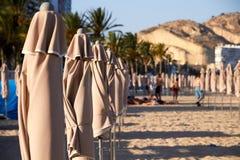 Playa mediterránea con algunos paraguas doblados imagen de archivo
