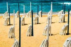 Playa mediterránea con las sillas y las sombrillas dobladas, concepto de ocio relajado fotos de archivo libres de regalías
