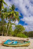 PLAYA MONTEZUMA, COSTA RICA, JUNE, 28, 2018: Outdoor view of small boat in the sand with some palm trees behind in Playa. Montezuma during gorgeous sunny day stock photos