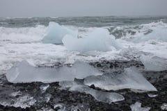 Playa negra de la arena con el iceberg Imagen de archivo