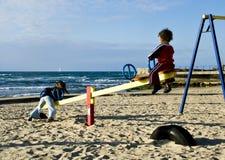 Playa, niños, oscilación Imágenes de archivo libres de regalías