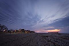 Playa nublada en la puesta del sol Foto de archivo