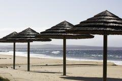 Playa Palapas del tejado cubierto con paja y vista al mar imagenes de archivo