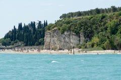 Playa pedregosa de la ciudad de Sirmione en el lago Garda con la vista de grutas de Catullus fotografía de archivo libre de regalías