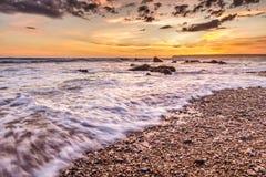 Playa pedregosa en la puesta del sol Fotografía de archivo libre de regalías