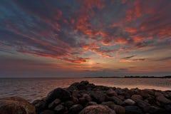 Playa pedregosa en puesta del sol Imágenes de archivo libres de regalías