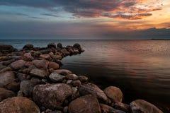 Playa pedregosa en puesta del sol Fotografía de archivo