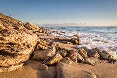 Playa pedregosa en un día soleado Imagenes de archivo