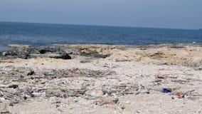 Playa rocosa con basura y basura Concepto de la contaminaci?n ambiental metrajes