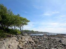 Playa rocosa con los árboles en la ensenada de Ryefield con las nubes en el cielo o Foto de archivo