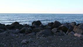 Playa rocosa del mar contra el cielo de la tarde Cámara estática metrajes