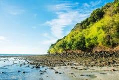 Playa rocosa durante marea baja con la selva tropical a un lado fotos de archivo