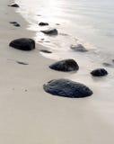 Playa rocosa en la puesta del sol Fotos de archivo libres de regalías