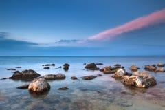 Playa rocosa hermosa del mar en la puesta del sol Fotos de archivo libres de regalías