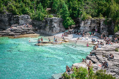 Playa rocosa natural asombrosa y agua clara azul tranquila con la gente que nada en el lago Fotos de archivo libres de regalías