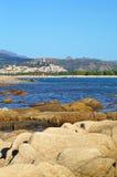Playa rocosa y pueblo en las montañas Foto de archivo