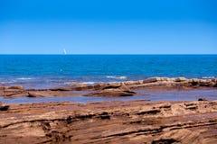 Playa rocosa y vela en el horizonte de mar Fotos de archivo