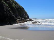 Playa rodeada por Rocky Cliffs y la línea de la playa fotos de archivo libres de regalías