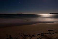 Playa romántica de la arena del ocesn del claro de luna, exposición larga Foto de archivo
