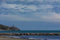 Playa, rompeolas y torre al día claro imagenes de archivo